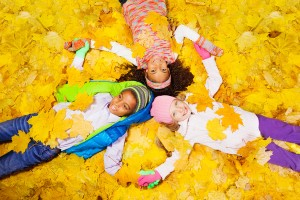 Three kids, girls and a boy laying on the ground covered with autumn maple orange leaves laying on the ground