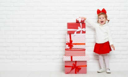 happy little girl child with Christmas gifts at a blank brick wall
