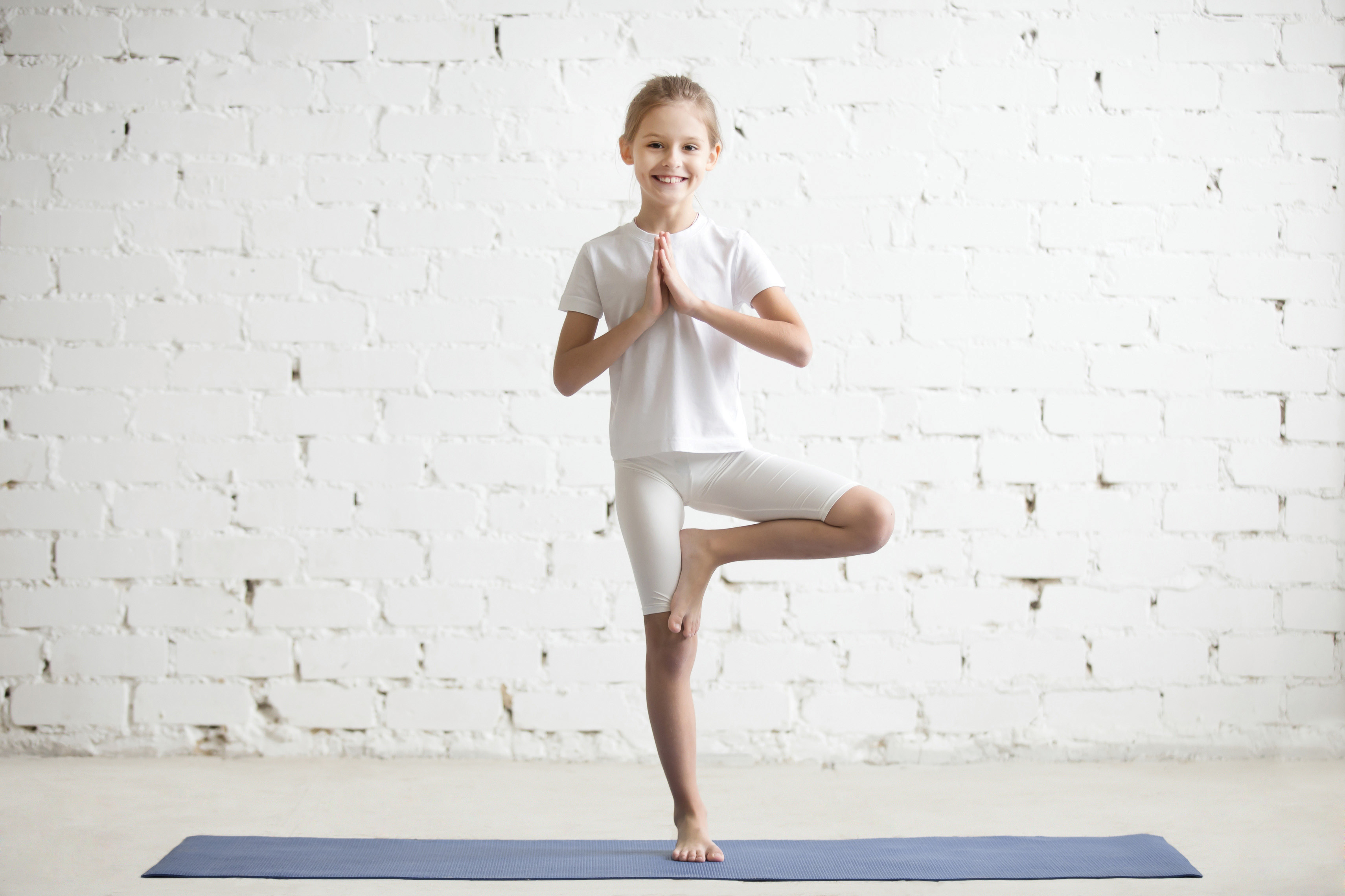 Girl child in Vrksasana pose, white studio background
